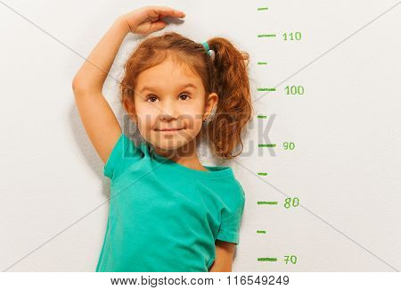 Close portrait of little girl standing by the scale drawn on the wall in living room and measure her height with hand