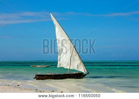 Wooden sailboat (dhow) on a tropical beach of Zanzibar island