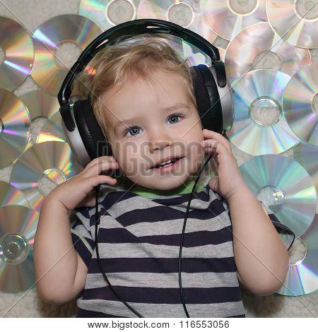 A Little Boy In Headphones Listens To Music. White Boy In Headphones Lying On Disks. Baby Listening