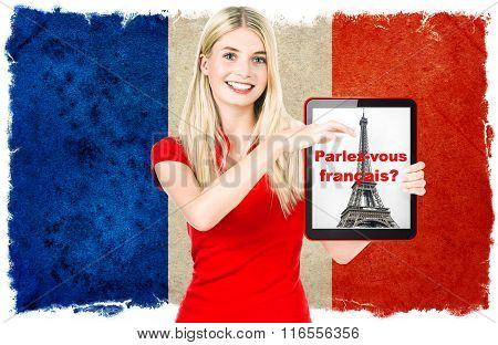 French language learning concept. Young woman with flag of France on the background holding tablet pc. Sample text Learn French! Collage