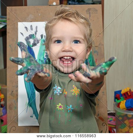 Small Child With Blue Eyes, Drawing Finger Paints. Babe Shows Palms Soiled In A Paint. Little Painte