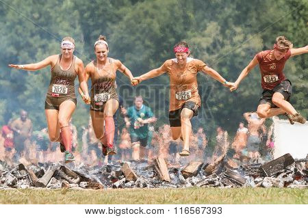 Women Hurdle Burning Logs Together In Extreme Obstacle Course Race