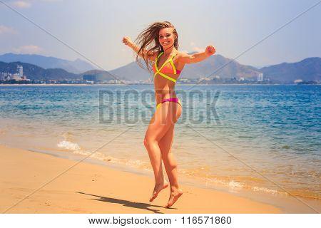Blonde Slim Girl In Bikini Poses On Tip Toe On Sand Beach