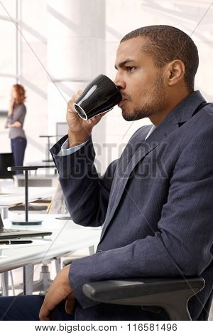 Serious afro american businessman drinking coffee at office. Sitting in chair, unsmiling. Side view, suit.