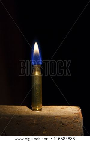 Cartridge On A Brick With A Flame Out Of The Top