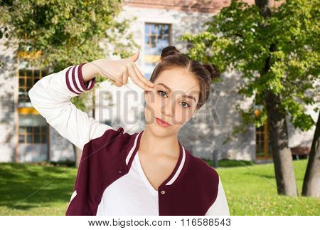bored teenage girl making finger gun gesture