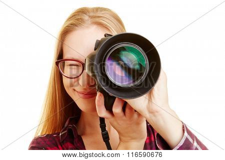 Smiling young woman with professional camera taking pictures