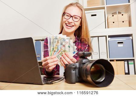 Successful woman with camera and computer earning money