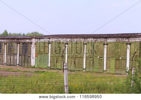 Fence Of Barbed Wire And Abandoned Military Facility At Cloudy Summer Day