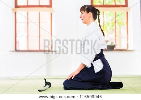 Woman sitting on mats while Aikido training in martial arts school
