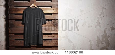Photo black tshirt  hanging in front of concrete wall. Wide