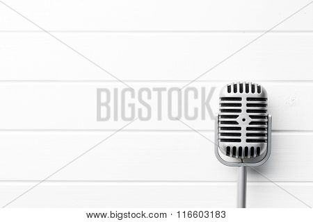 vintage microphone on white wooden background