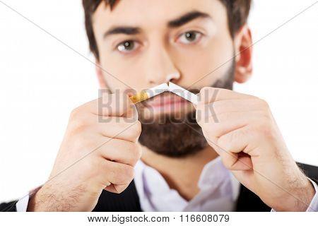 Businessman breaking a cigarette.