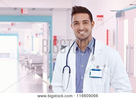 Happy young physician doctor standing at hospital hallway. Smiling, looking at camera, wearing stethoscope and lab coat. Copyspace.