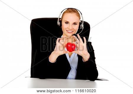 Happy phone operator woman holding heart toy