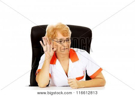 Smile elderly female doctor or nurse sitting behind the desk and overhears a conversation poster