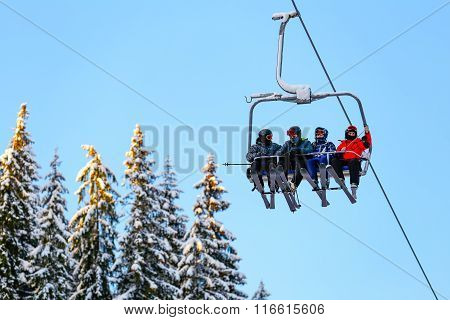 Bottom view ski family on chair lift