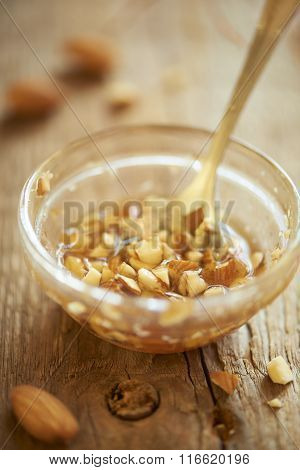 Chopped almonds and honey in glass bowl