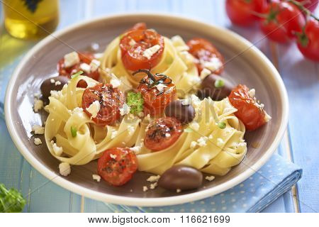 Pasta with roasted tomatoes, olives and feta cheese, italian cuisine