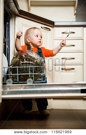 Cute baby helping mother unload dishwasher in kitchen poster