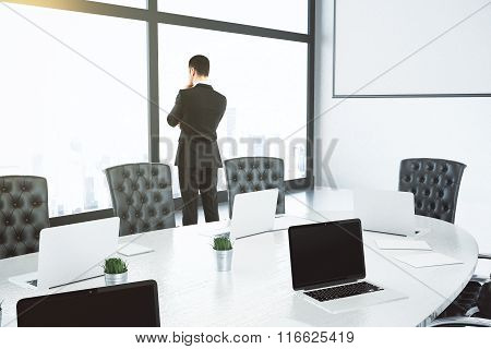 Businessman Thinks And Looks Out Big Window In Conference Room With Oval Table And Leather Chaiirs