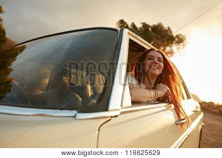 Portrait of happy young woman going on a road trip leaning out of window. Female enjoying travelling in a car with her boyfriend. poster