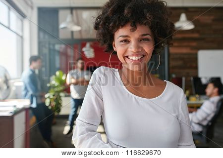 Smiling Young African Businesswoman With People In Background