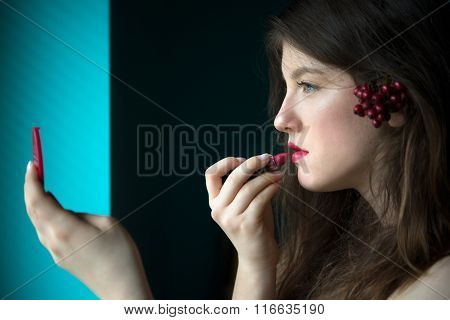 Beautiful Young Woman Putting On Lipstick
