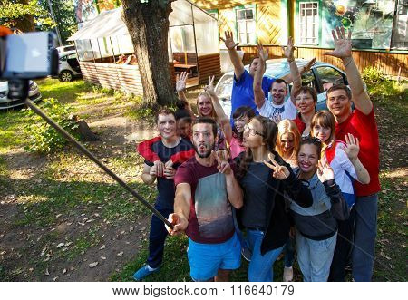 Group Of Friends Taking Selfie With Selfie Stick Outdoors