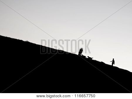 Shadows of 2 people and dog going to the mountain in dark sky background. People silhouette on night