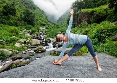 Woman doing Ashtanga Vinyasa yoga asana Utthita trikonasana - extended triangle pose outdoors at waterfall in Himalayas