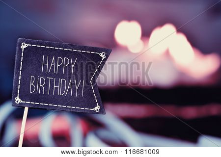 closeup of a black flag-shaped signboard with the text happy birthday, and a birthday cake with lit candles in the background