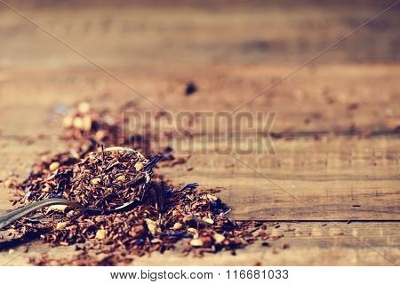closeup of a spoon with rooibos mixed with flowers, dry fruits and herbs, to prepare a rooibos tea, on a rustic wooden table
