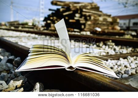 closeup of an open book on the railroad tracks, with a filter effect