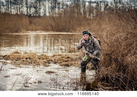 hunter man creeping through the swamp lurking in the bushes and shows gesture to be quiet