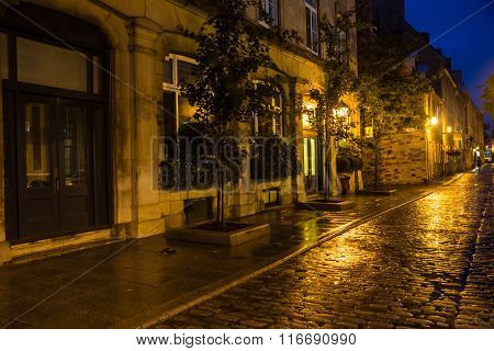 Cobblestone street in old Quebec on a rainy night.