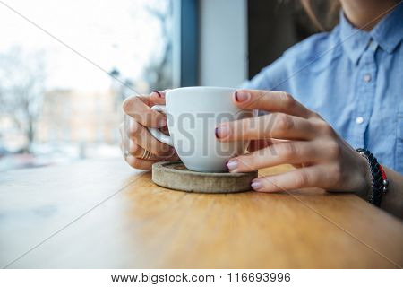 Closeup of white cup on wooden coster holded by woman hands on the table near the window