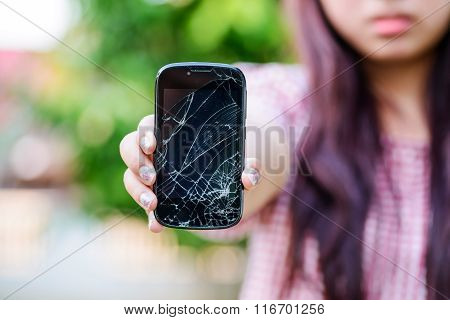 Girl hand holding cracked mobile smartphone, damage mobile phone
