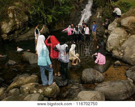 Muslim day-trippers relax in the Ciliwung River in Puncak West Java Indonesia