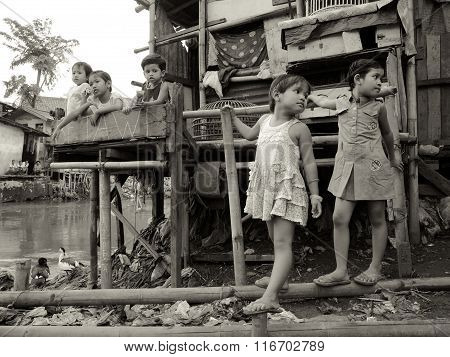 Young children outside their slum house by a polluted river in Jakarta, Java