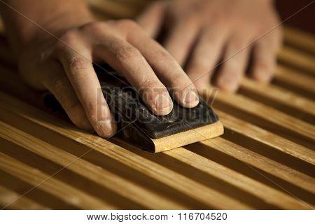 Male hands sanding wooden slats