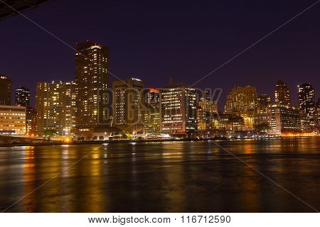 Manhattan skyscrapers with colorful reflections in East River at night.