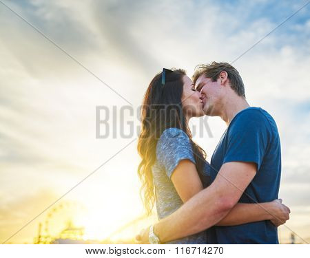 couple kissing in front of santa monica california at sunset