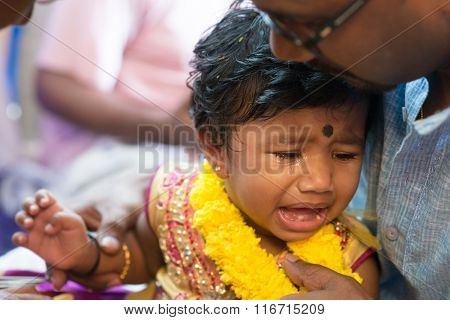 Father pampered his baby girl that crying in the karnavedha events. Traditional Indian Hindus ear piercing ceremony. India special rituals.