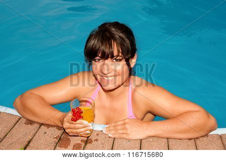 woman in a swimmingpool with a glass in her hand