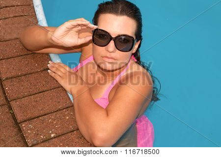 Summer portrait of a beautiful  girl with sun glasses in the swimming pool