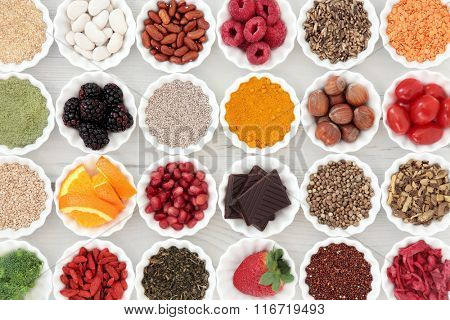 Super health food selection in porcelain crinkle bowls over distressed wooden background. High in vitamins and antioxidants.