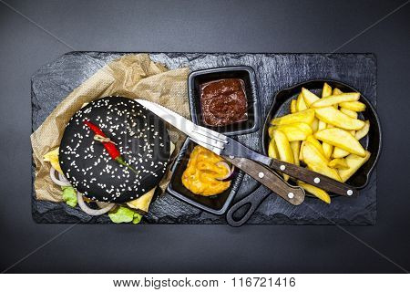 Black burger. Set of the black burger. Stone plate with: black burger roll slices of juicy marble beef,  cheese, fresh salad with French fries on a cast-iron griddle, with chili sauce and guakomole.
