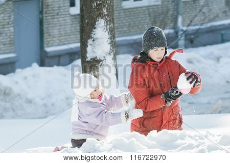 Two children playing outdoors with plastic toy tool in snowy winter sunny day