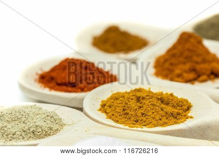 Wooden spoons filled with spices